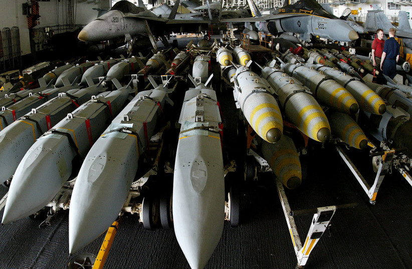 Aviation ordonancemen stand next to JSOW (Joint Standoff Weapon) (left) and JDAM satellite guided bombs (right) aboard the USS Kitty Hawk aircraft carrier in the northern Gulf April 9, 2003 (credit: YVES HERMAN/REUTERS)