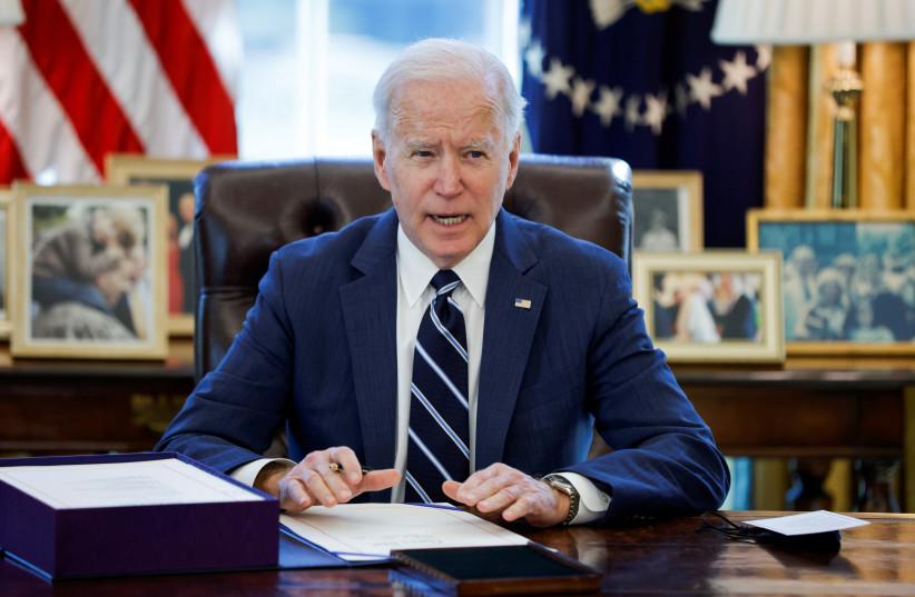 Presiden AS Joe Biden menandatangani Rencana Penyelamatan Amerika, paket tindakan bantuan ekonomi untuk menanggapi dampak pandemi penyakit virus corona (COVID-19), di dalam Ruang Oval di Gedung Putih di Washington, AS, 11 Maret 2021. (kredit: REUTERS/TOM BRENNER)