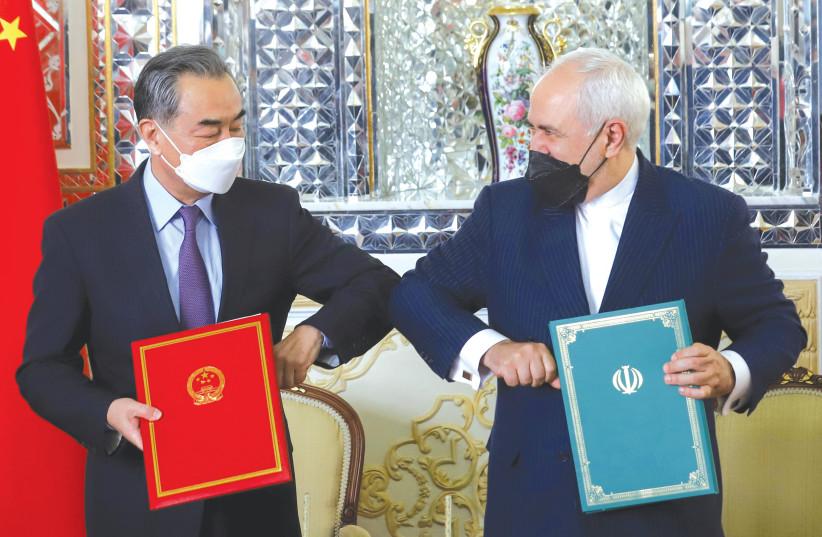 LE MINISTRE IRAN DES AFFAIRES ÉTRANGÈRES Mohammad Javad Zarif et le ministre chinois des Affaires étrangères Wang Yi se sont cognés les coudes lors de la cérémonie de signature d'un accord de coopération de 25 ans, à Téhéran, en mars. (crédit photo : MAJID ASGARIPOUR/WANA/REUTERS)