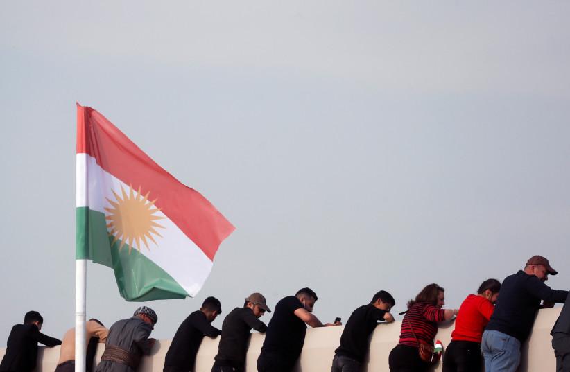 Des gens se tiennent à côté d'un drapeau du Kurdistan en attendant que le pape François tienne une messe au stade Franso Hariri d'Erbil, en Irak, le 7 mars 2021. (Crédit photo : REUTERS/YARA NARDI)