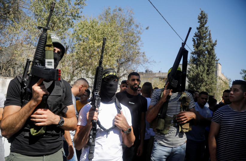 Islamic Jihad gunmen attend a funeral of one of the Palestinians killed late Saturday night in clashes with the IDF in the West Bank village of Burqin. (credit: REUTERS/RANEEN SAWAFTA)