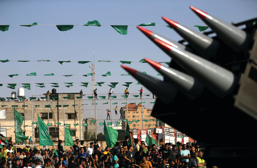 HAMAS SUPPORTERS attend an anti-Israel rally as rockets are displayed on a truck in Rafah, in the southern Gaza Strip in May. (credit: IBRAHEEM ABU MUSTAFA/REUTERS)
