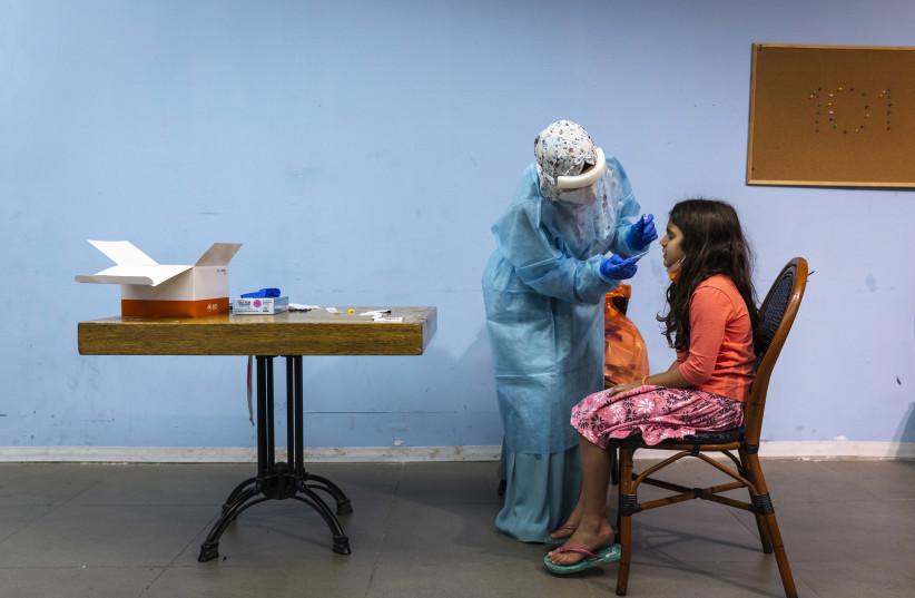 Magen David worker take a COVID-19 rapid antigen test from Israelis, at a Magen David Adom testing center in Jerusalem, on September 26, 2021.  (credit: OLIVIER FITOUSSI/FLASH90)