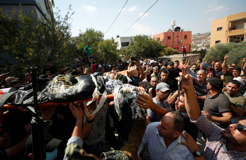 Des Palestiniens portent le corps du tireur du Jihad islamique Alaa Zyoud qui a été tué par les forces israéliennes lors d'un échange de tirs lors d'un raid, lors de ses funérailles près de Jénine, le 30 septembre 2021. (Crédit photo : REUTERS/MOHAMAD TOROKMAN)