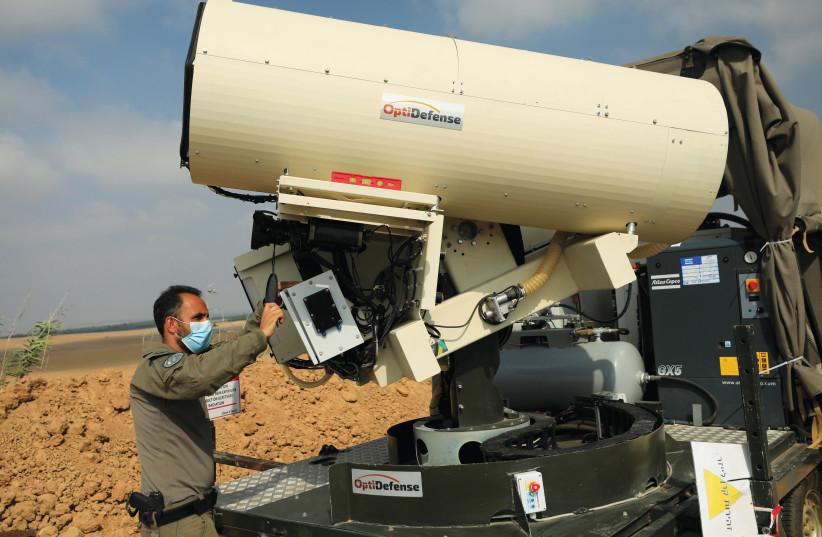 Un officier de police frontalier vérifie une unité à un système laser visant à intercepter des ballons incendiaires, près de la frontière de Gaza. (crédit : AMIR COHEN/REUTERS)