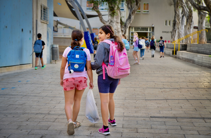 Young Israeli students arrive for their first day of school after the holidays, at Gabrieli school, in Tel Aviv.  September 30, 2021.  (photo credit: AVSHALOM SASSONI/FLASH90)
