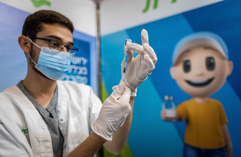 Health worker prepares a Covid-19 vaccine at a temporary Clalit health care center in Jerusalem, October 3, 2021.  (credit: YONATAN SINDEL/FLASH90)