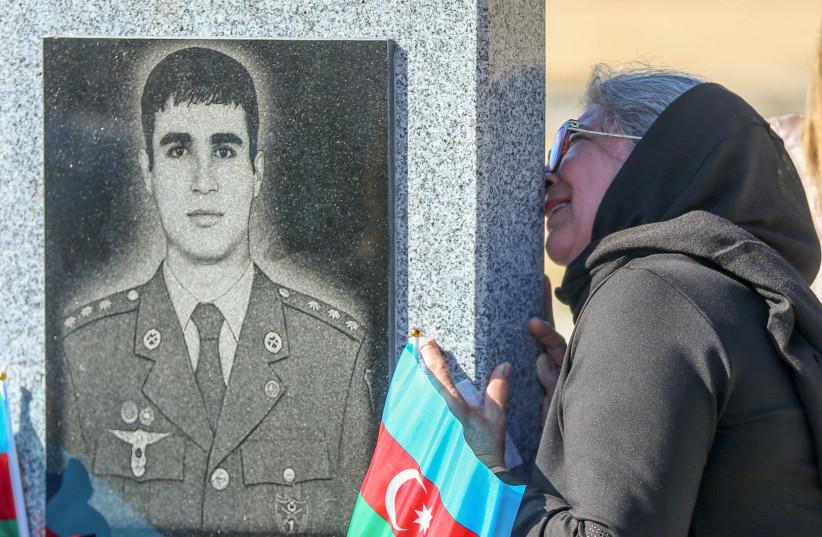 Une femme pleure dans un cimetière lors d'une commémoration pour le militaire azéri tué dans un conflit dans la région du Haut-Karabakh à l'occasion de son premier anniversaire, à Bakou, en Azerbaïdjan, le 27 septembre 2021. (Crédit: REUTERS/AZIZ KARIMOV)