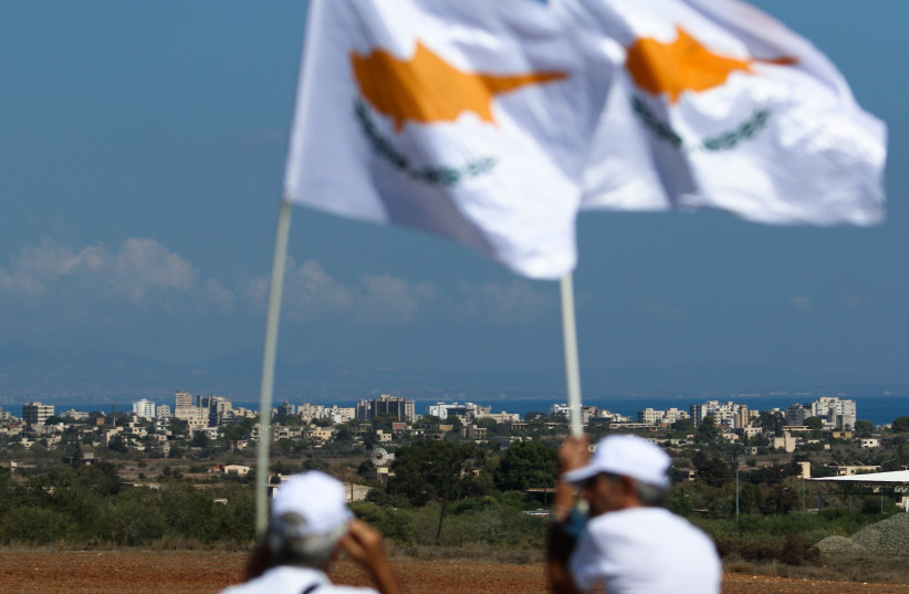 Protestors look on at Varosha while holding up Cyprus flags during a rally calling for peace in Dherinia, Cyprus October 3, 2021. (credit: REUTERS/YIANNIS KOURTOGLOU)