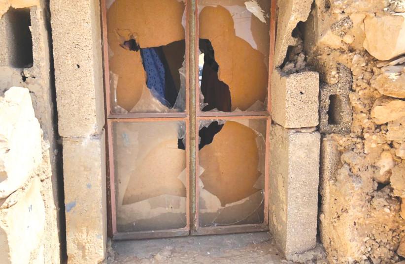 ONE OF the shattered windows in Hamamdeh family's stone home in Khirbet al-Mufaqarah. (credit: TOVAH LAZAROFF)