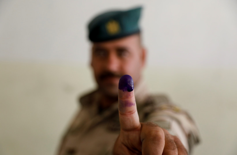 An Iraqi Security forces member shows his inked finger as he casts his vote at a polling station, two days before polls open to the public in a parliamentary election, in Mosul, Iraq October 8, 2021.  (credit: REUTERS/KHALED AL-MOUSILY)