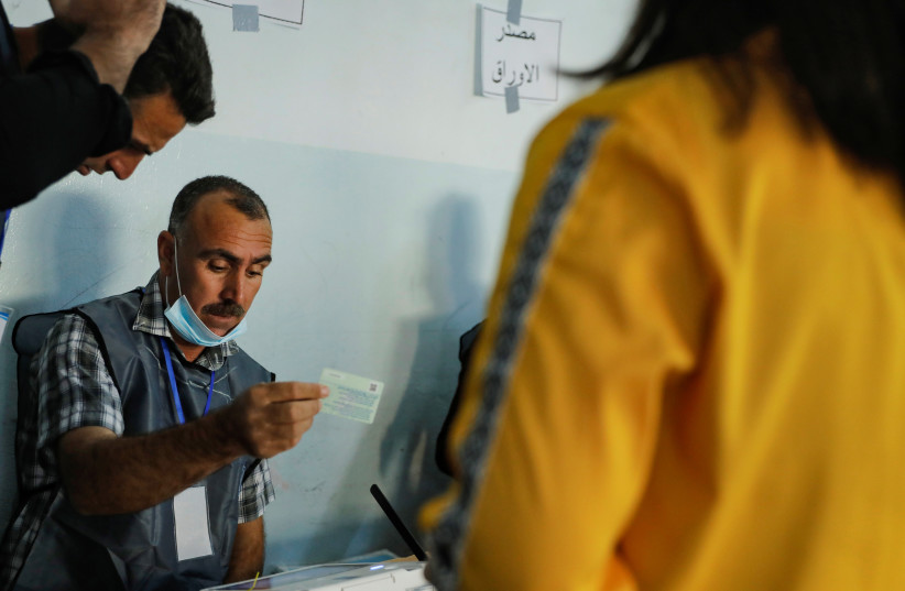 Poll workers double check the identification card of a voter at a polling station during the parliamentary election, in Qaraqosh, Iraq, October 10, 2021. (credit: REUTERS/ABDULLAH RASHID)