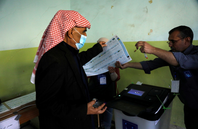 A voter hands a ballot paper to a poll worker at a polling station, as Iraqis go to the polls to vote in the parliamentary election, in Mosul, Iraq October 10, 2021. (credit: REUTERS/KHALED AL-MOUSILY)