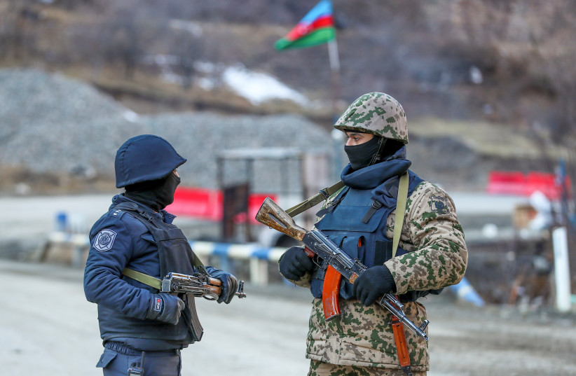 An Azeri soldier and police officer talk as they stand guard at the Kalbajar district, Azerbaijan, December 21, 2020 (photo credit: AZIZ KARIMOV/REUTERS)