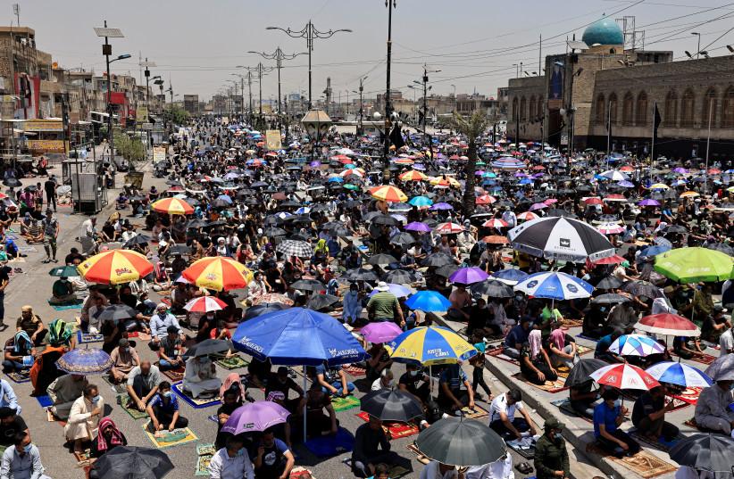 Supporters of Iraqi Shi'ite cleric Moqtada al-Sadr attend Friday prayers in Baghdad's Sadr City, Iraq July 2, 2021. (credit: REUTERS/THAIER AL-SUDANI)