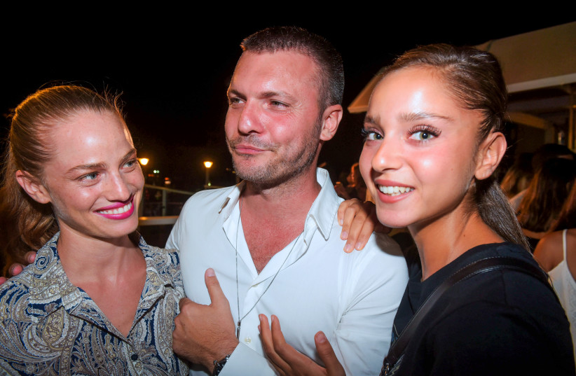 Israeli modeling agent Shai Avital (C) poses for a picture with Israeli models during an event on a rooftop in Tel Aviv, on September 17, 2017 (photo credit: AVSHALOM SASSONI/FLASH90)