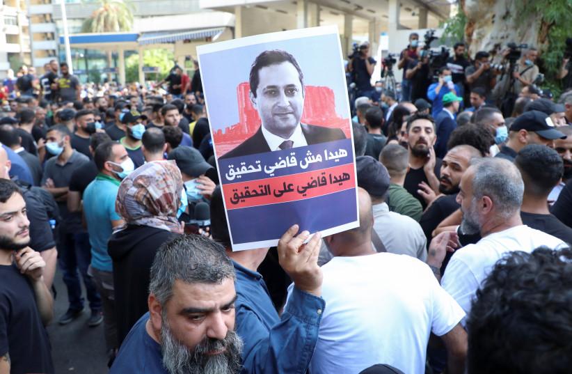 Des partisans des groupes chiites libanais Hezbollah et Amal et du mouvement chrétien Marada participent à une manifestation contre Tarek Bitar, le juge principal de l'enquête sur l'explosion du port, près du palais de justice de Beyrouth (crédit : MOHAMED AZAKIR/REUTERS)
