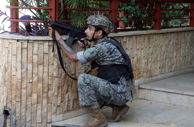 Un soldat de l'armée prend position après que des coups de feu ont éclaté sur un site près d'une manifestation qui commençait contre le juge Tarek Bitar, qui enquête sur l'explosion du port de l'année dernière, à Beyrouth, au Liban, le 14 octobre 2021. (Crédit photo : REUTERS/MOHAMED AZAKIR)