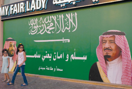 GIRLS STAND next to a poster depicting Saudi Arabia's King Salman bin Abdulaziz Al Saud (right) and Crown Prince Mohammed bin Salman in Jeddah, Saudi Arabia, 2017.
