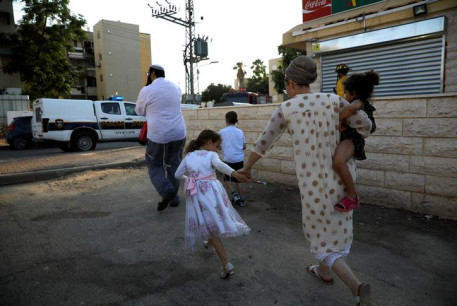 Israelis run for shelter as a siren sounds during a rocket attack at the southern city of Sderot July 14, 2018