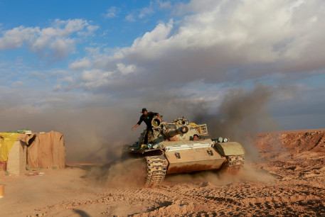 Iranian-backed militias stand on a tank close to the Syria-Iraq border