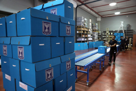 People sort ballot boxes as part of preparations for the upcoming Israeli election, during a briefing for members of the media at the Israel Central Election Committee Logistics Center in Shoham, Israel