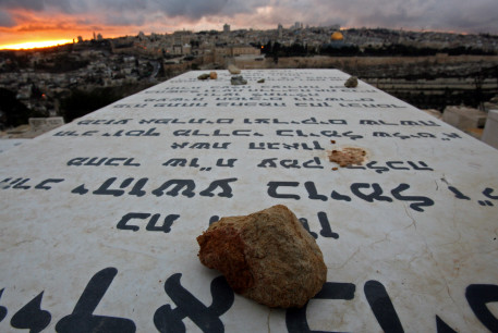 Stones placed in remembrance lie on grave tablets on the Mount of Olives Jewish cemetary as the sun sets in Jerusalem