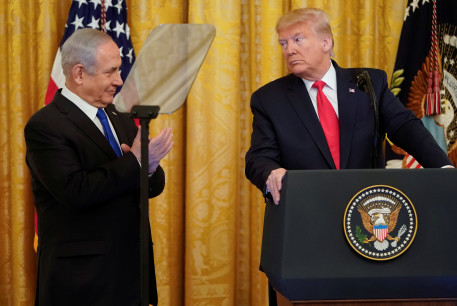 U.S. President Donald Trump looks over at Israel's Prime Minister Benjamin Netanyahu during a joint news conference to announce a new Middle East peace plan proposal in the East Room of the White House in Washington, U.S., January 28, 2020