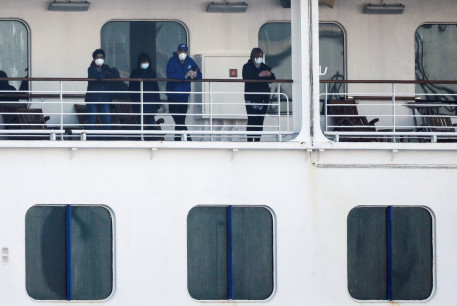 Passengers wearing mask are seen on the cruise ship Diamond Princess, as the vessel's passengers continue to be tested for coronavirus, at Daikoku Pier Cruise Terminal in Yokohama, south of Tokyo, Japan February 13, 2020