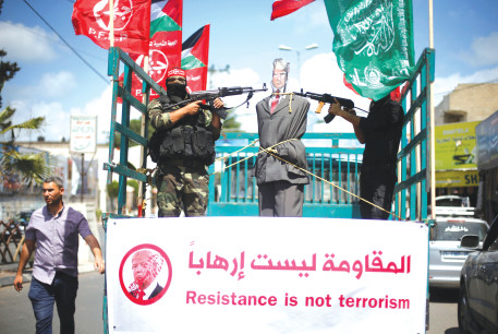 MEMBERS OF the Popular Front for the Liberation of Palestine (PFLP) aim their weapons at an effigy depicting US President Donald Trump as they ride a truck during a protest in Gaza City.