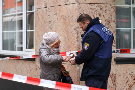 A police officer helps a woman to light a candle to place it on a makeshift memorial outside one of the crime scenes following a shooting in Hanau, near Frankfurt, Germany, February 20, 2020