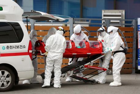 A confirmed coronavirus patient is wheeled to a hospital at Chuncheon, South Korea, February 22, 2020.