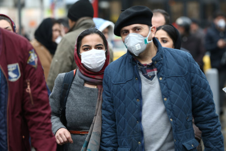 Iranian couple wearing protective masks to prevent contracting a coronavirus walk at Grand Bazaar in Tehran, Iran