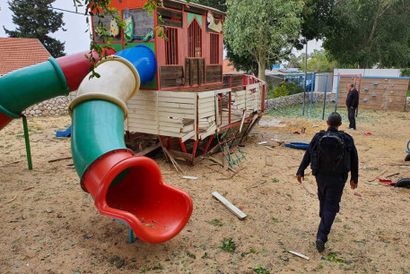 Israel Police and bomb disposal experts investigate a children's playground where rockets landed.