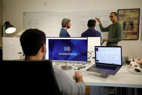 Employees of the D-ID startup company work at the company's office in Tel Aviv