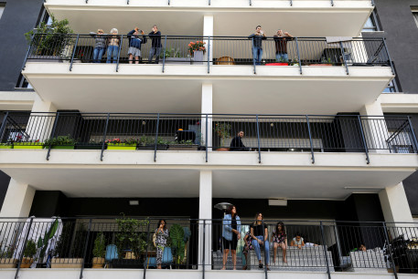 Residents stand on their balcony as they watch Israeli soldiers performing for them in a bid to assist civilians observing government stay-at-home orders to help fight the spread of the coronavirus disease (COVID-19) in Tel Aviv, Israel April 7, 2020.