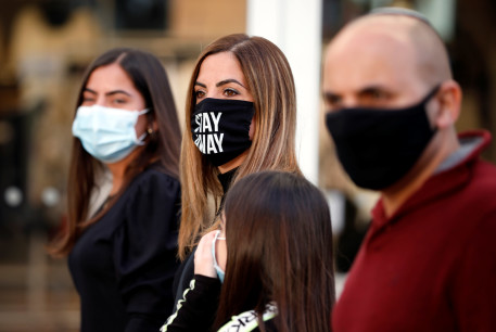 Shoppers wear face masks and walk around a fashion shopping center in Ashdod, as restrictions over the coronavirus disease (COVID-19) ease around Israel, May 5, 2020.