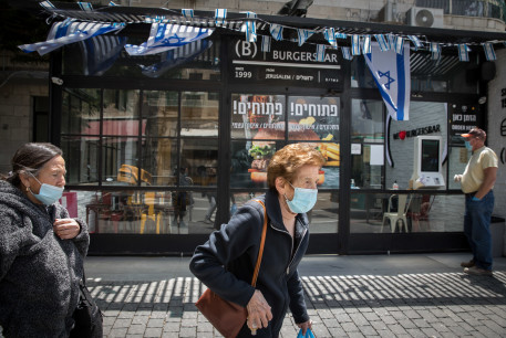 Israelis wearing face masks and gloves, walk outside an open restaurant proposing take aways and deliveries  takes away on May 06, 2020 in Jerusalem.