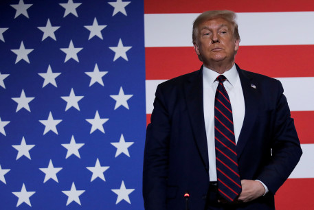 US President Donald Trump stands in front of a US flag as he participates in a roundtable on donating plasma during a visit to the American Red Cross National Headquarters in Washington, US, July 30, 2020