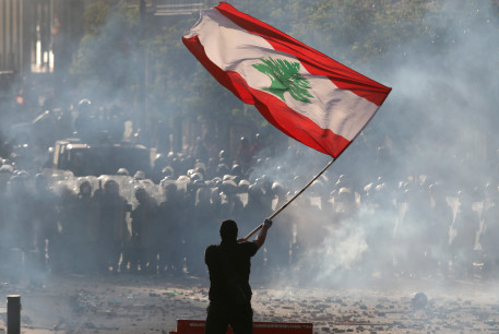 A demonstrator waves the Lebanese flag in front of riot police during a protest in Beirut, Lebanon, August 8, 2020