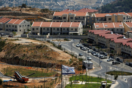 The Israeli national flag flutters as apartments are seen in the background in the Israeli settlement of Efrat in the West Bank August 18, 2020.