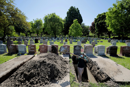 Roberto Arias prepares a grave for burial at Woodlawn Cemetery during the coronavirus disease (COVID-19) outbreak in Everett, Massachusetts, US, May 27, 2020.
