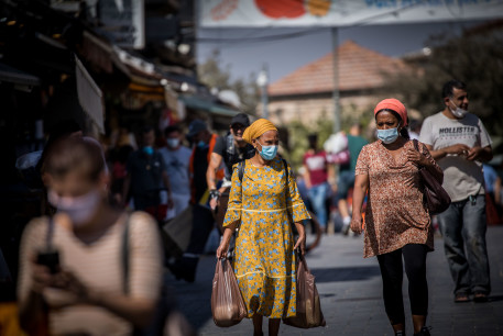 People wearing face masks shop at the Mahane Yehuda Market in Jerusalem on October 7, 2020, during a nationwide lockdown to prevent the spread of COVID-19