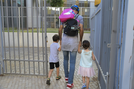 Parents accompany their children to the kindergarten in Tel Aviv as they return to kindergarden on October18, 2020 after being shut down during a national lockdown in a means to prevent the spread of the Coronavirus.