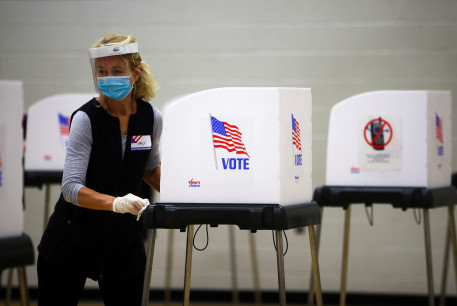 A woman cleans a voting booth at a polling station located at the McFaul Activity Center in Bel Air, Harford County, during early voting in Maryland, US, October 27, 2020