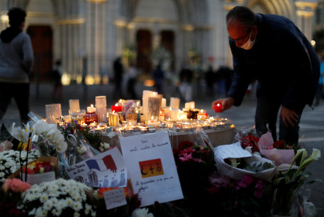A man lights a candle near the Notre Dame church in tribute to the victims of a deadly knife attack in Nice, France, October 30, 2020