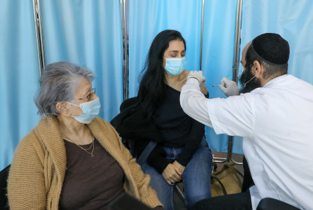People get vaccinated at the Clalit vaccination center in Jerusalem, January 3, 2020.