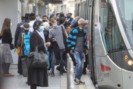 Israelis are seen boarding the light rail on Jaffa Street in Jerusalem after the coronavirus lockdown ends, on February 8, 2021.
