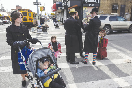 A FAMILY pauses in the street as people celebrate Purim in Brooklyn earlier this month.
