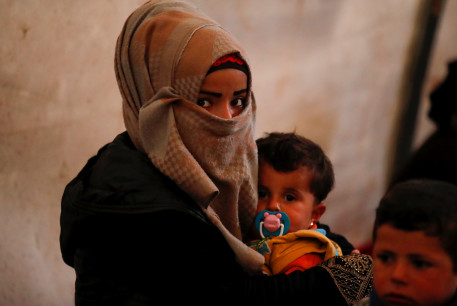 An internally displaced Syrian woman and her children sit in a tent in an IDP camp located near Idlib